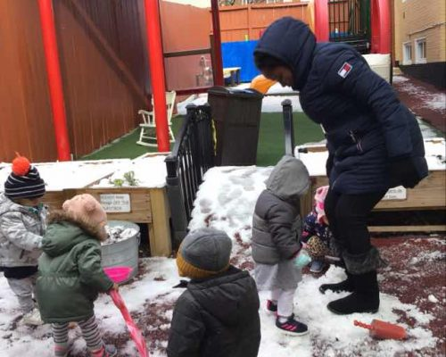 Group of young little kids wearing jackets while shoveling and playing with snow with teacher at the playground at a Preschool & Daycare Serving Washington, DC
