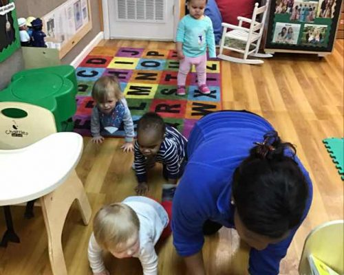 Divers group of toddlers crawling on the floor together with teacher, toddlers playing at a Preschool & Daycare Serving Washington, DC
