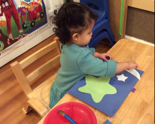Young little one showing artistry putting stars and a Moon paper cutouts on a piece of colored paper at a Preschool & Daycare Serving Washington, DC