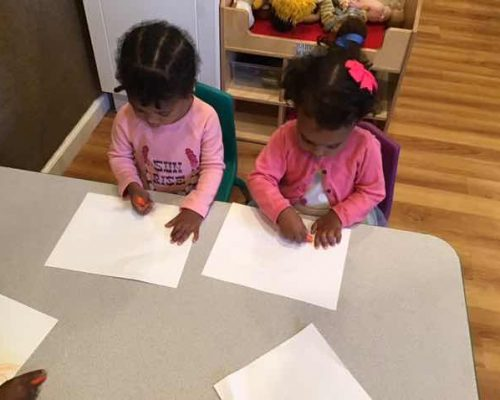 Two little African american preschool girls wearing pink outfit doing some coloring and drawing on a piece of paper in art their art activity at a Preschool & Daycare Serving Washington, DC