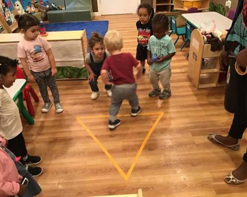 Group of diverse little children enjoy playing while being watched by a teacher inside classroom at a Preschool & Daycare Serving Washington, DC