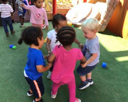 Diverse young little kids in circles enjoy playing while holding each others hands at a Preschool & Daycare Serving Washington, DC