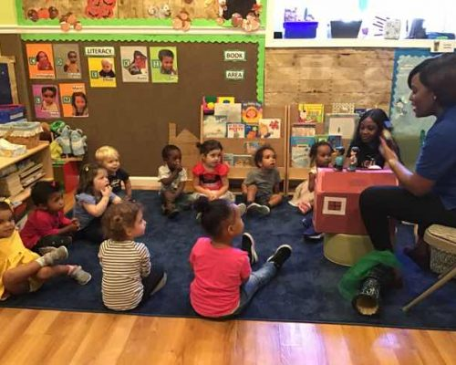 African american teacher in front of group of toddlers showing kids toys while storytelling at a Preschool & Daycare Serving Washington, DC