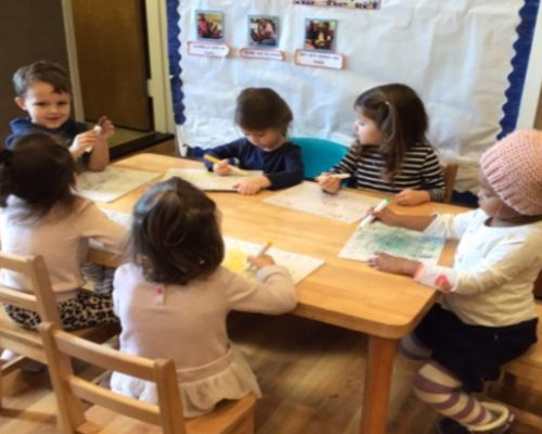 Group of preschoolers in art class, drawing and coloring inside classroom at a Preschool & Daycare Serving Washington, DC