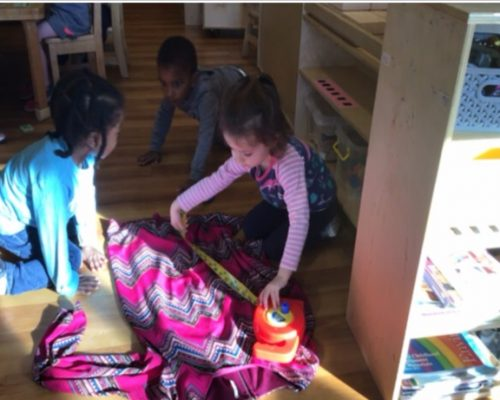 Little ones learning how to measure using a measuring tape on a clothes at a Preschool & Daycare Serving Washington, DC