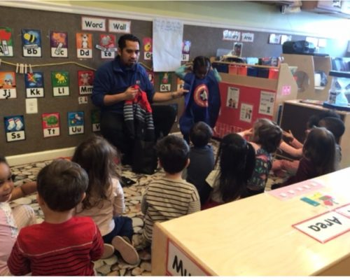 Teacher in front with an African american kid boy wearing a superhero outfit in front of group of young little kids at a Preschool & Daycare Serving Washington, DC
