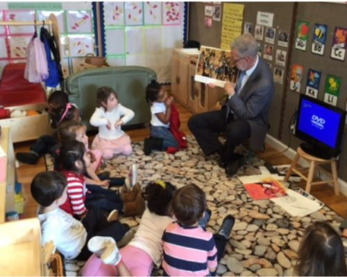 Teacher showing group of diverse young kids pictures in a storytelling books at a Preschool & Daycare Serving Washington, DC