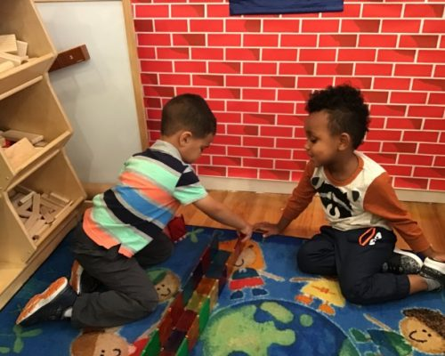 Two little young kid boys playing with colored wooden building blocks at a Preschool & Daycare Serving Washington, DC