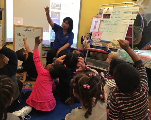 Young little preschoolers raising hands to answer teacher's question at a Preschool & Daycare Serving Washington, DC