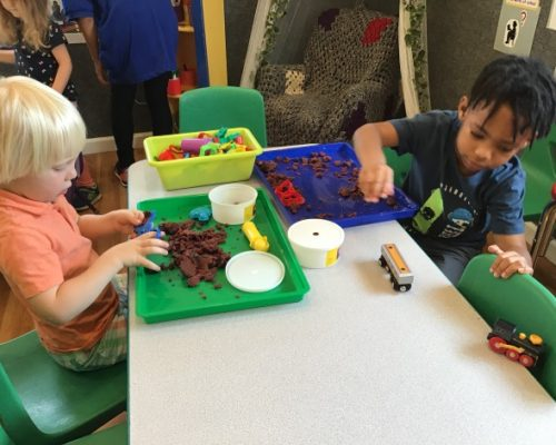 Young little kids in art class playing with clay and toy trains at a Preschool & Daycare Serving Washington, DC